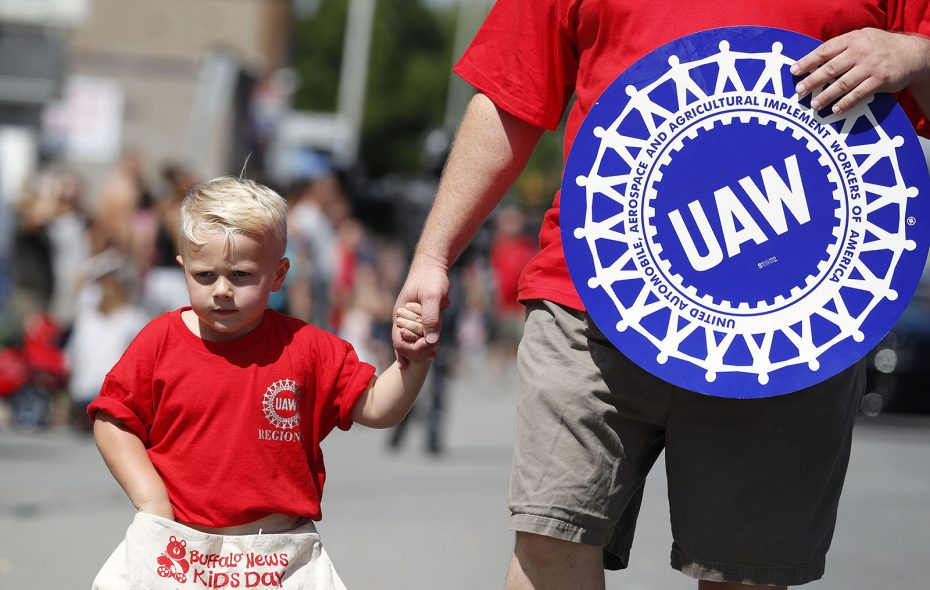 Evan Chamberlain, 4, walks with Scott Lohouse and the UAW workers in the 2018 Labor Day parade. (Mark Mulville/News file photo)