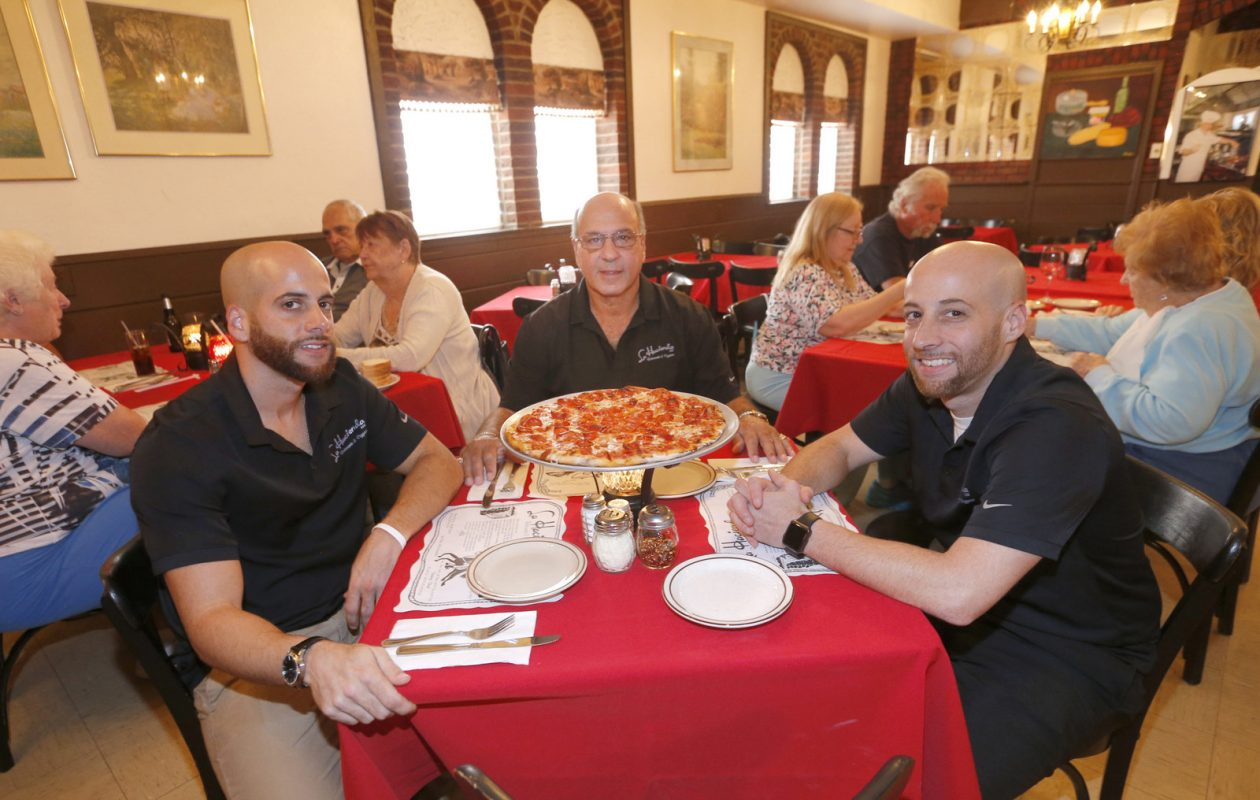 Owners, from left, Shawn, George and Christopher Satarian ready to relax with a pizza at La Hacienda.  (Robert Kirkham/Buffalo News)