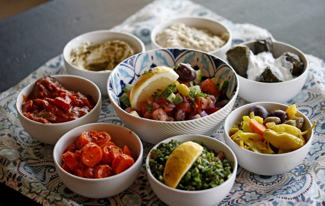 Clockwise from top: babaganoush, grape leaves with tzatziki, pickled cabbage, tabouli, Moroccan carrots, Turkish eggplant salad and lebneh yogurt spread, Traditional Maza arranged around a chopped salad at Or by Falafel Bar. (Robert Kirkham/Buffalo News)