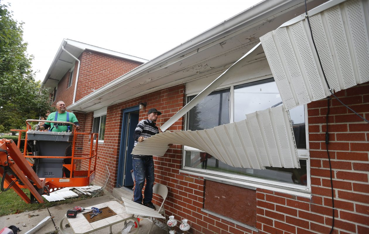Workers Frank Ramos left, and Alex Rivera renovate the exterior of an apartment at the Towne Gardens complex. (Mark Mulville/Buffalo News)