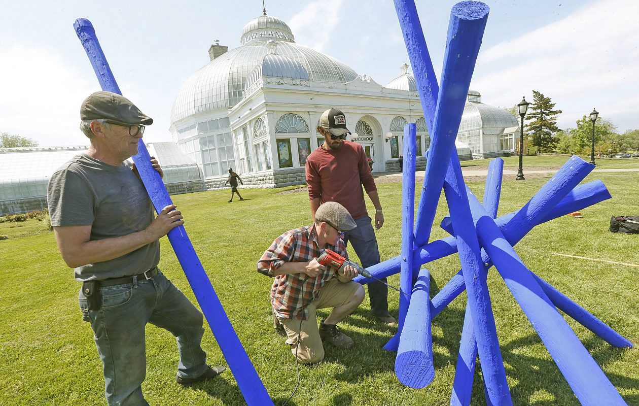 Artist Shayne Dark, left, waits to place the next part of his piece, 'Tanglewood,' as assistants Colin Smith, drilling, and Eric Jones help with the installation at the Botanical Gardens in 2015. Dark's piece is coming to Amhert's Bassett Park next.  (Robert Kirkham/Buffalo News file photo)