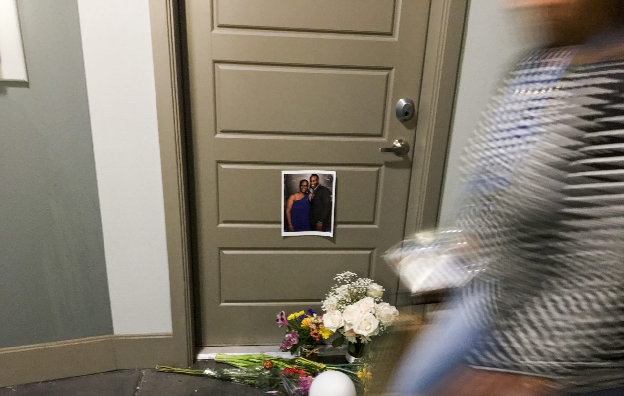 A resident passes flowers at the front door of Botham Shem Jean, who Dallas police say was shot Thursday by Amber Guyger, an off-duty police officer who mistakenly thought her apartment was his, as photographed on Monday, Sept. 10, 2018 at the South Side Flats in Dallas, Texas. Guyger was in uniform. (Shaban Athuman/Dallas Morning News/TNS)