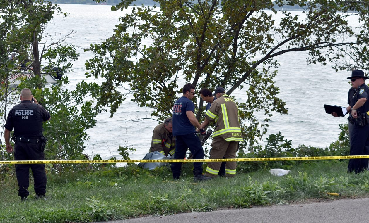 Niagara County sheriff's deputies, State Park Police officers and Niagara Falls firefighters investigate a body found on the bank of the upper Niagara River on Saturday, Sept. 1, 2018. (Larry Kensinger/Special to The News)