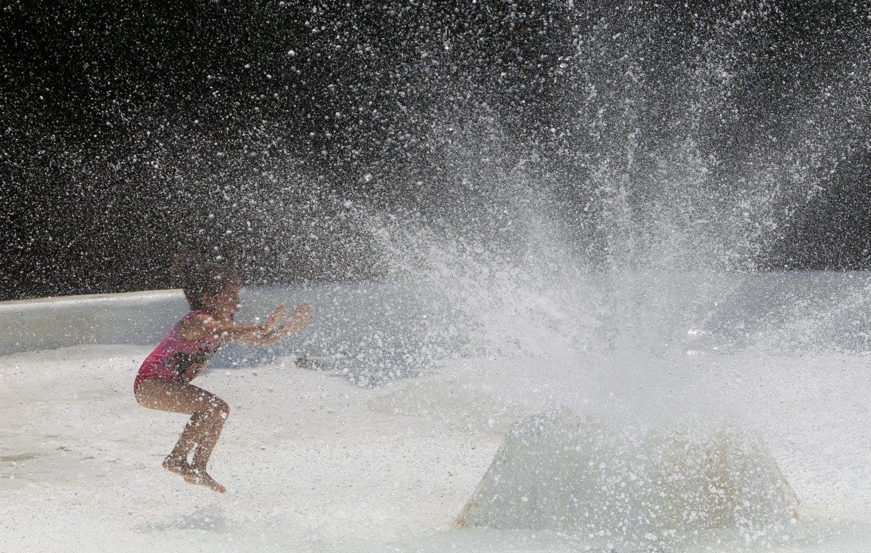 Rayine Moore, 3, is simply delighted with the splash pad at the Asarese-Matters Community Center, Wednesday, July 3, 2013. (Sharon Cantillon/Buffalo News)
