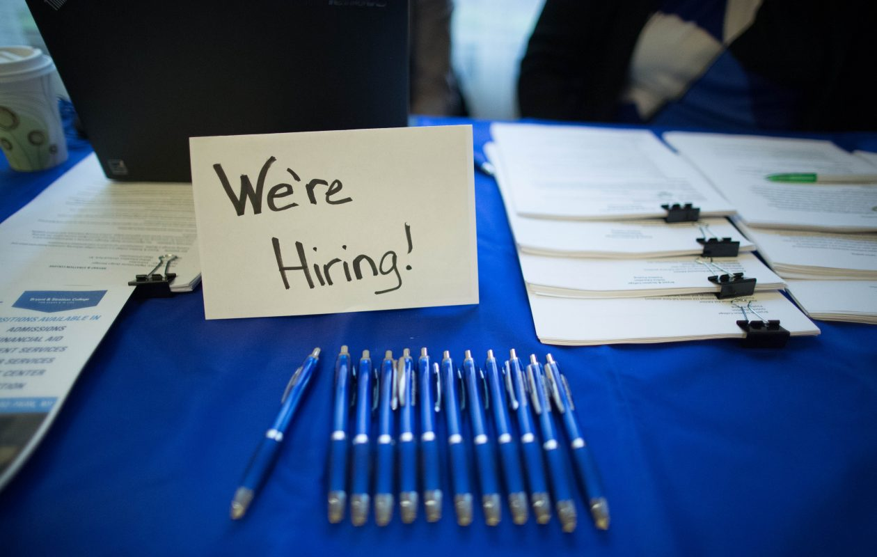 A sign advertising employment on a vendor's table during the Jobsapalooza career fair at the Buffalo Niagara Marriott in Amherst. (Derek Gee/News file photo)