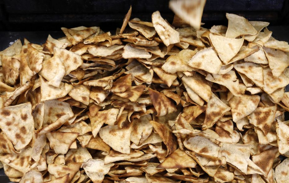 Freshly baked pita chips fall into bins after baking in a seven-burner tunnel oven at Cedars Bakery. (Derek Gee/Buffalo News)