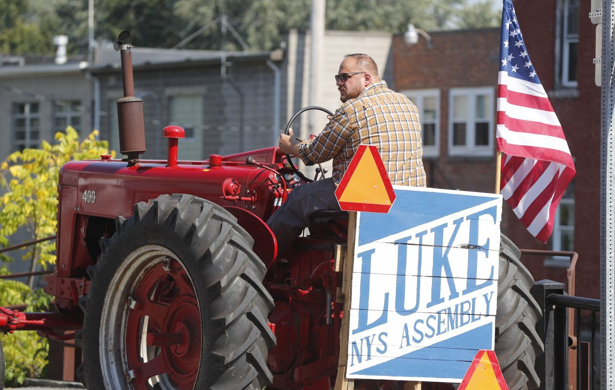 New York State Assembly candidate Luke Wochensky rides a red tractor through Attica on a tour of the district on Friday, Sept. 21, 2018. (Mark Mulville/Buffalo News)