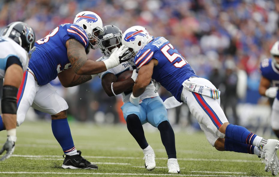 Bills defensive tackle Star Lotulelei and linebacker Lorenzo Alexander tackle Tennessee Titans running back Dion Lewis. (Mark Mulville/News file photo)