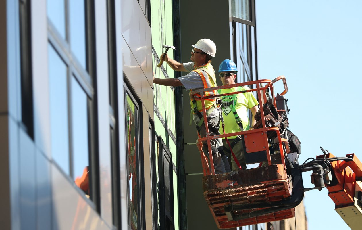 Ed Verent, left, and Matt Colvin of Home Team Renovation do exterior work on Nineteen North, a luxury apartment building on North Street in Buffalo, on what was a warm and sunny Wednesday. (Sharon Cantillon/Buffalo News)