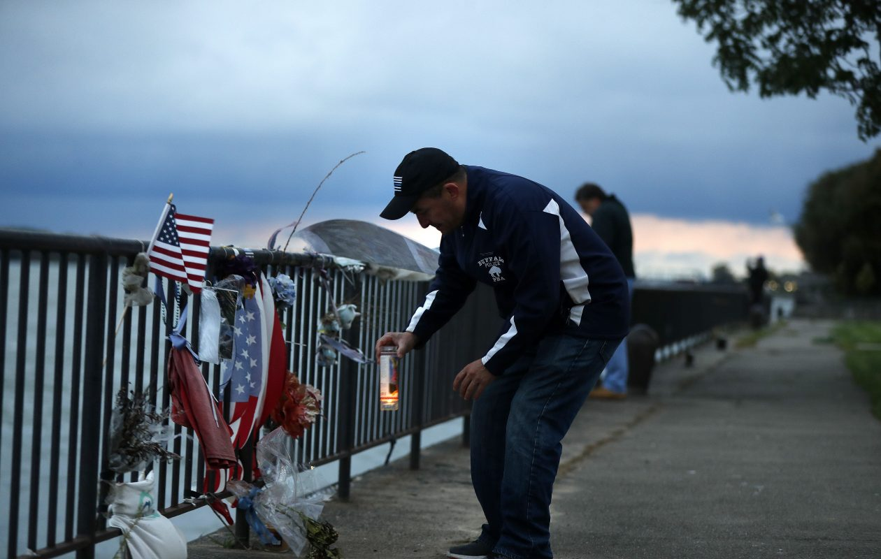Buffalo Police Officer David Rodriguez places a candle of St. Michael the Archangel at a memorial for officer Craig Lehner at Broderick Park on Wednesday, Oct. 17, 2018. St. Michael is the patron Saint of the police.    (Mark Mulville/Buffalo News)