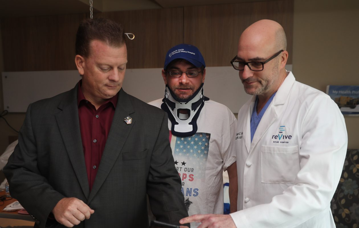 Navy vet Mike Sformo, left, with veteran Kurt Santini of Virginia, center, who underwent free neck surgery performed by Dr. Franco Vigna at Kenmore Mercy Hospital as part of Sformo's Operation Backbone. (John Hickey/Buffalo News)