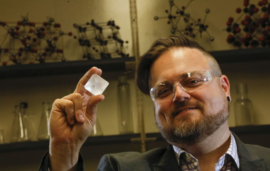 Jason Benedict, UB associate professor of chemistry, holds up an aluminum potassium sulfate crystal. He founded the U.S. Crystal Growing Competition which attracted more than 250 registered teams from 42 states and Washington, D.C., in the contest's fifth year. (Derek Gee/Buffalo News)