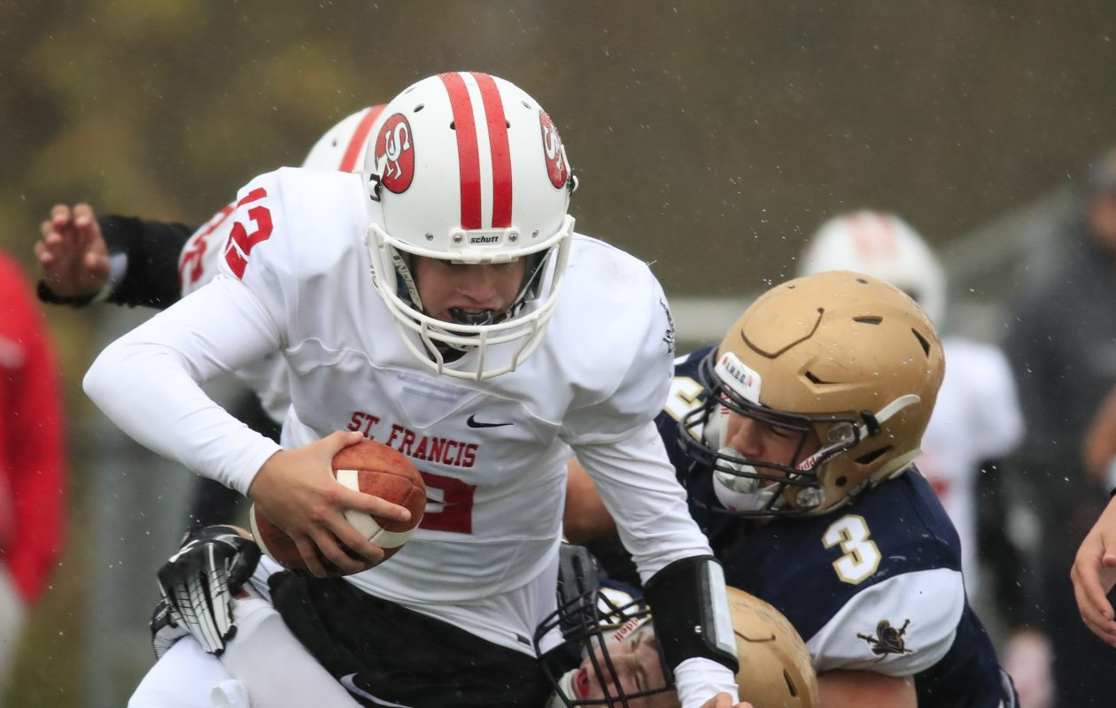 St. Francis quarterback Jake Ritts is sacked by Canisius' Joel Nicholas (3) and Tristian Vandenberg during Saturday's game at the Stransky Complex. (Harry Scull Jr./ Buffalo News)