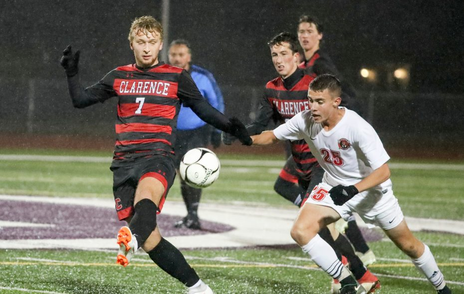 Clarence's Quinn Neelon battles Lancaster's Ben Walleshauser for the ball in the first half in Section VI AA boys soccer final Saturday (James P. McCoy/Buffalo News)