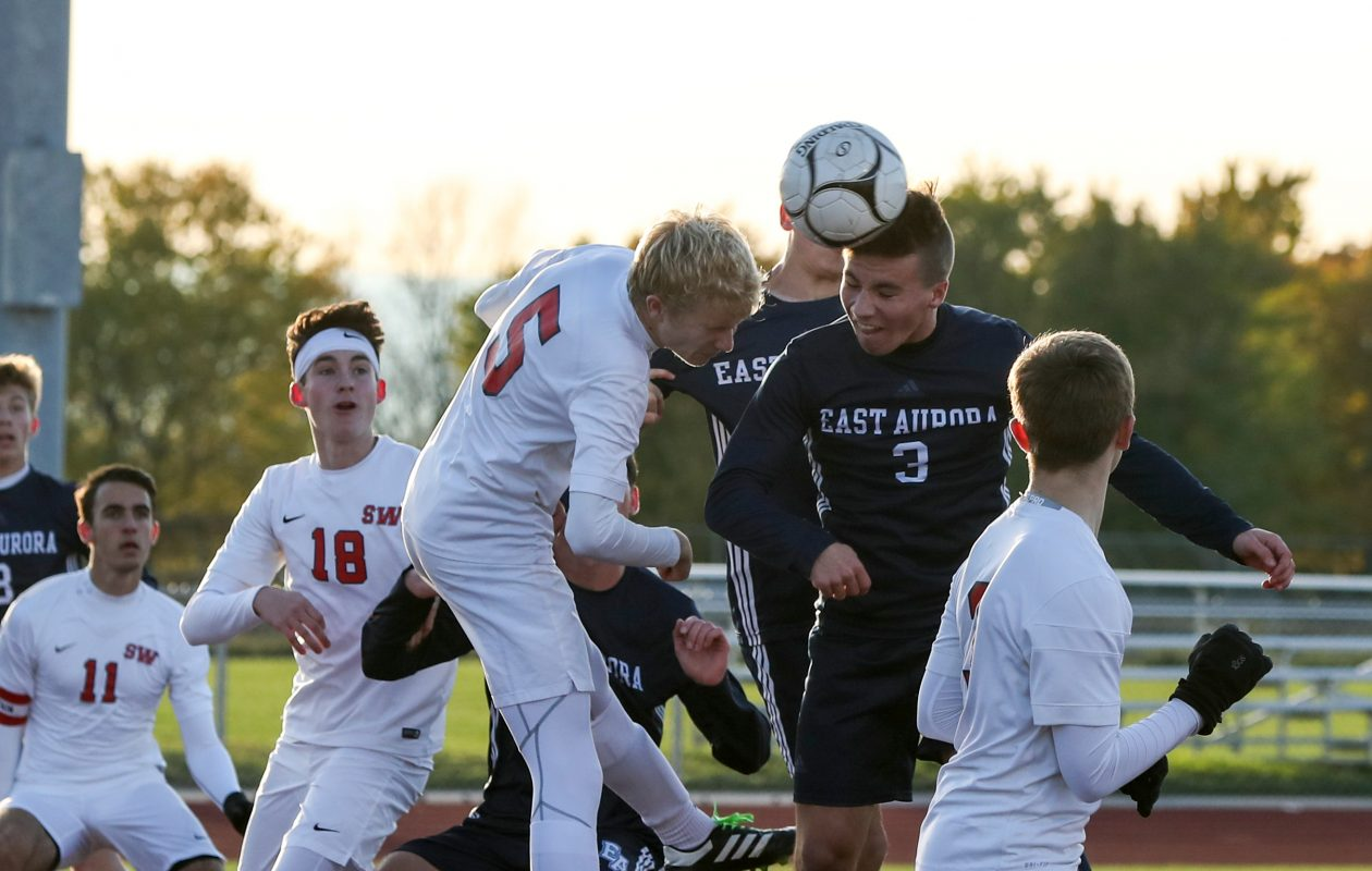 East Aurora's Jonathon Putney, second from right, heads the ball past Southwestern's Addison Pope, 5, for a goal in the first half at Tonawanda High School in Tonawanda on Tuesday. (James P. McCoy/Buffalo News)
