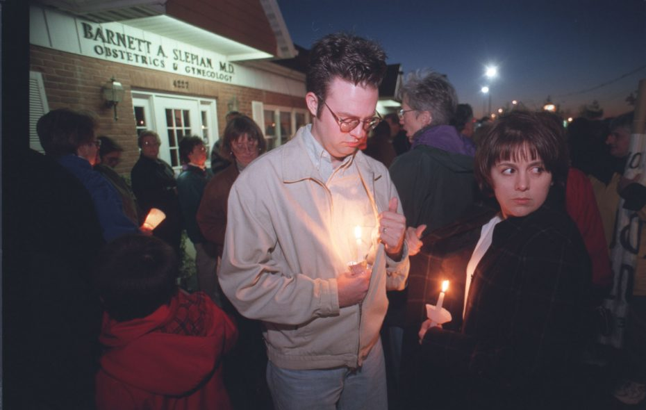 Kevin Grauke, left, and Catherine Collins were among those mourning the murder of Dr. Barnett Slepian in a candlelight vigil outside of his office on Maple road in Amherst after his killing in October 1998. (News file photo)