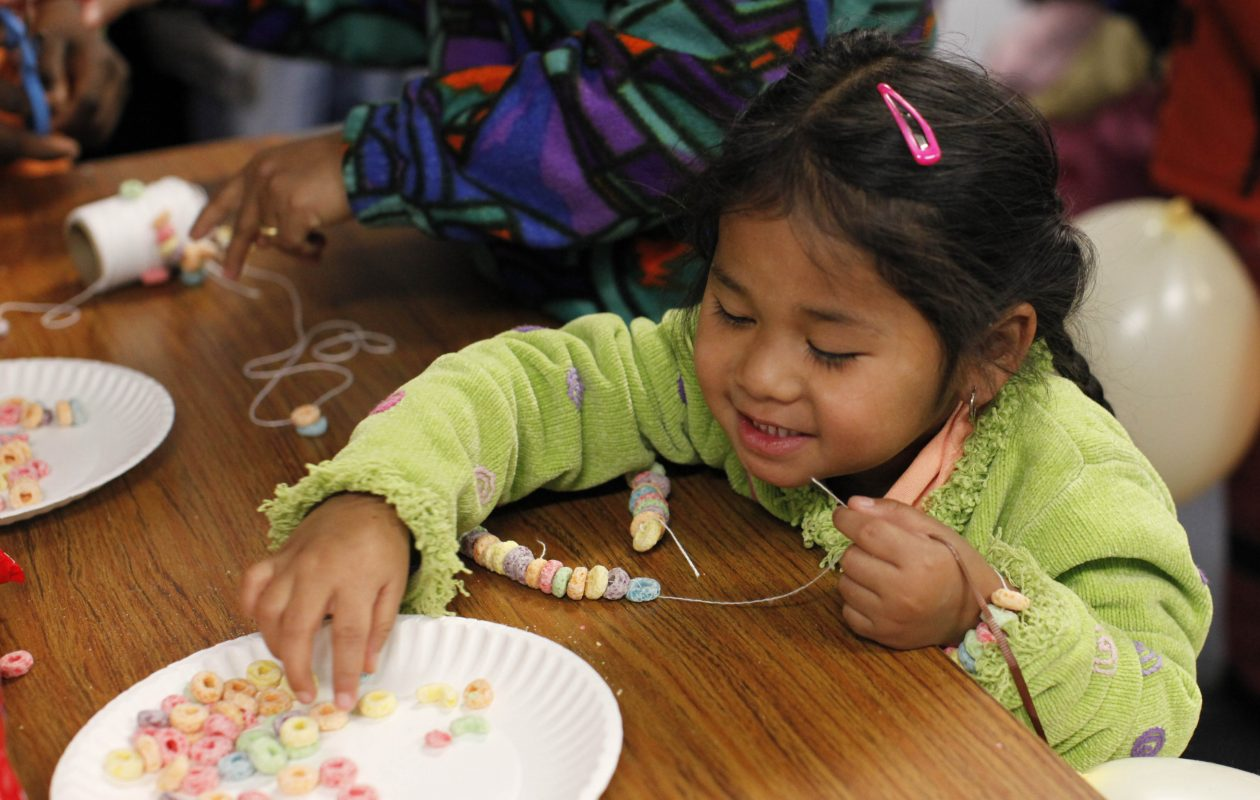 Eh Paw, 5, of Burma, makes a necklace out of fruit cereal during a Thanksgiving dinner for refugees hosted by Journey's End Refugee Services. (Photo by Derek Gee/News file photo)