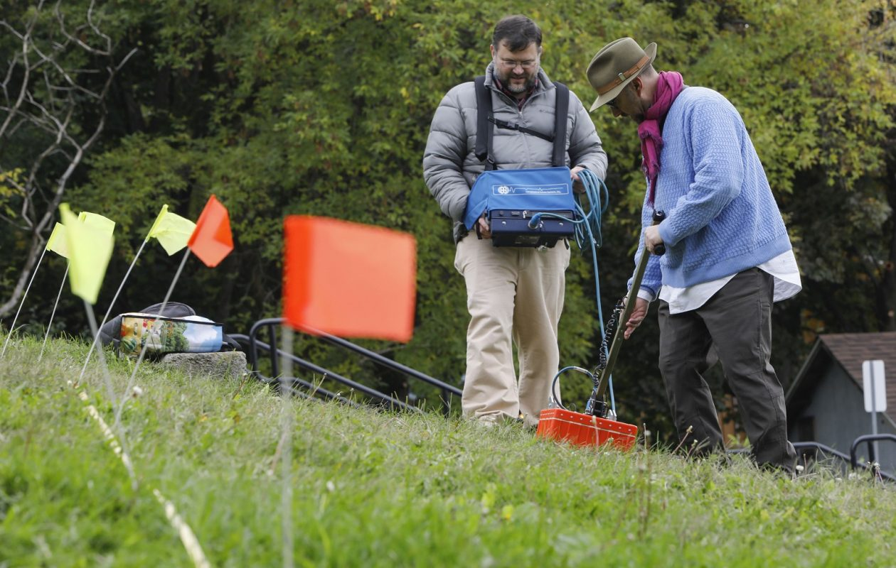 Volunteer Michael Beam, left, and Kevin Williams, associate professor in earth sciences at SUNY Buffalo State, use ground penetrating radar to scan the ground in an attempt to locate a car/time capsule. (Derek Gee/Buffalo News)