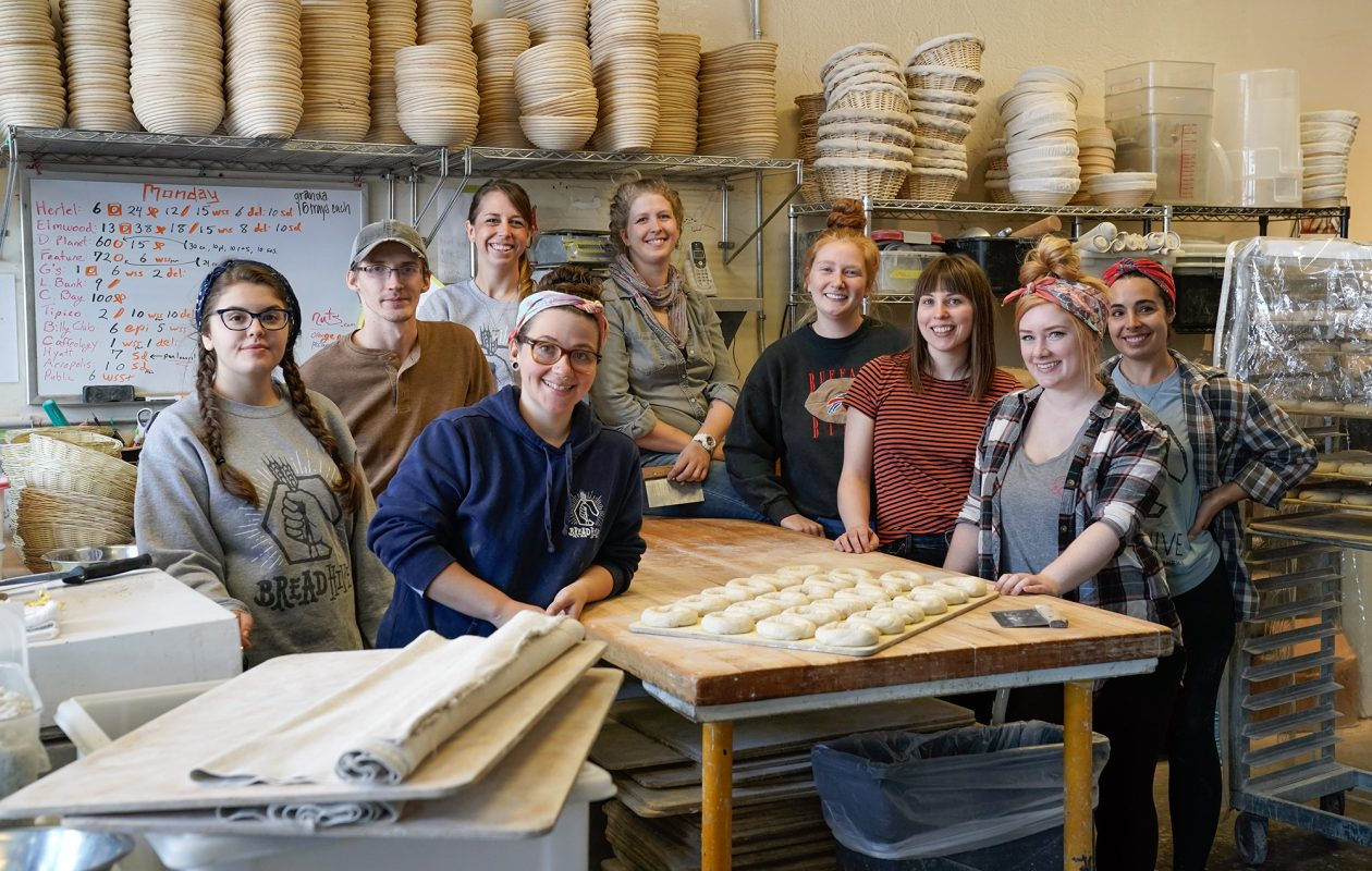 The nine employee-owners of BreadHive gather around the prep table in their bakery on Baynes St. on Buffalo's West Side. The owners bake the bread, staff the shop and make all decisions for the company by consensus. (Dave Jarosz)