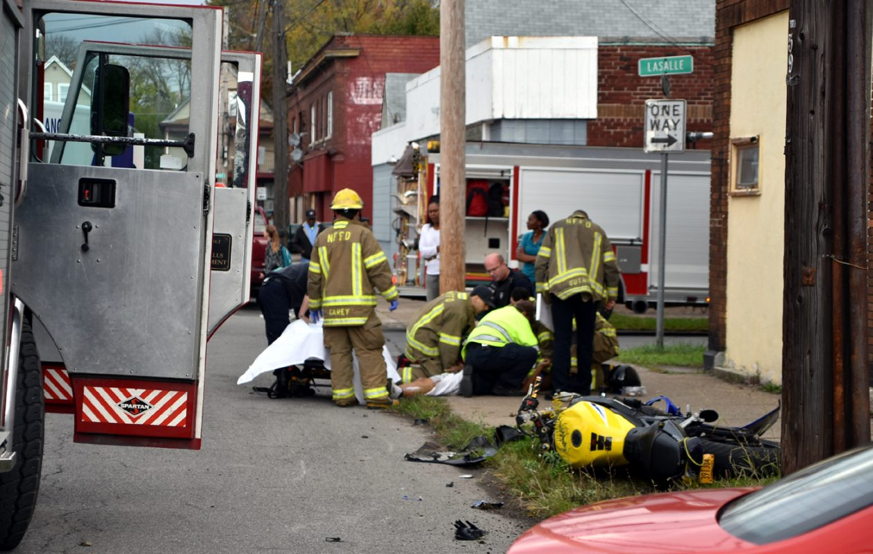 Rescue workers provide medical treatment to a person injured when a car and a motorcycle collided at 2:37 p.m. Tuesday, Oct. 23, 2018, at 19th Street and LaSalle Avenue in Niagara Falls. (Larry Kensinger/Special to The News)