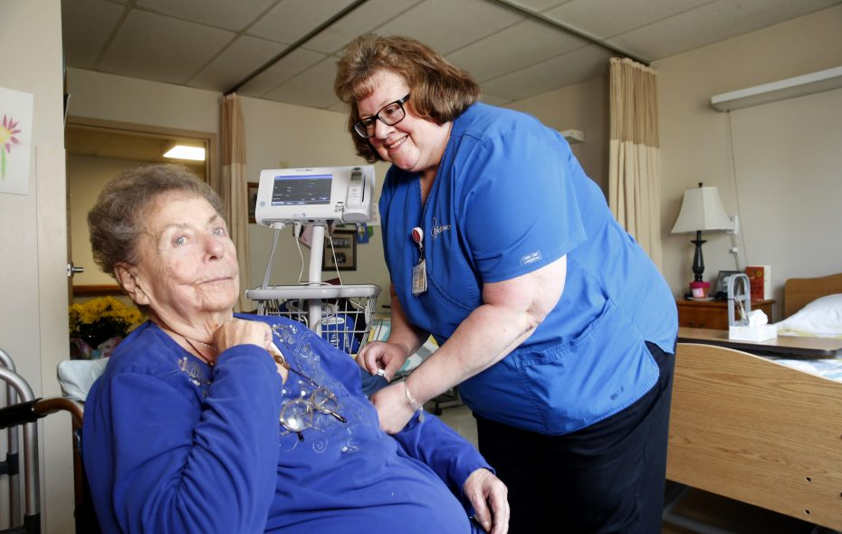 """Licensed practical nurse Gail Over checks in on resident Charlotte Martin, 86, at the Elderwood at Lancaster nursing home in Lancaster on May 17, 2018. The nursing home was one of 11 in Erie and Niagara counties designated as a """"best nursing home"""" by U.S. News and World Report on Oct. 30, 2018. (Robert Kirkham/Buffalo News)"""