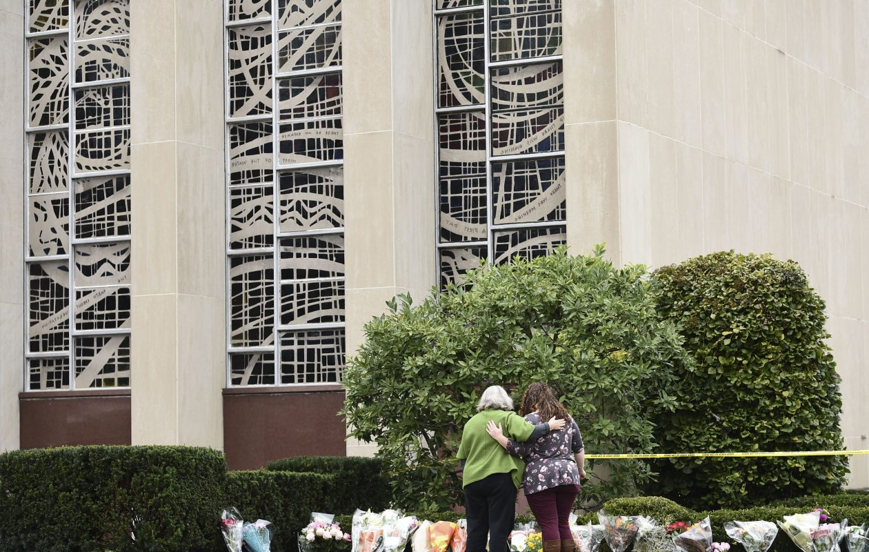 Women embrace in front of memorial flowers Sunday outside of the Tree of Life Synagogue in Pittsburgh. (Brendan Smialowski/AFP/Getty Images)