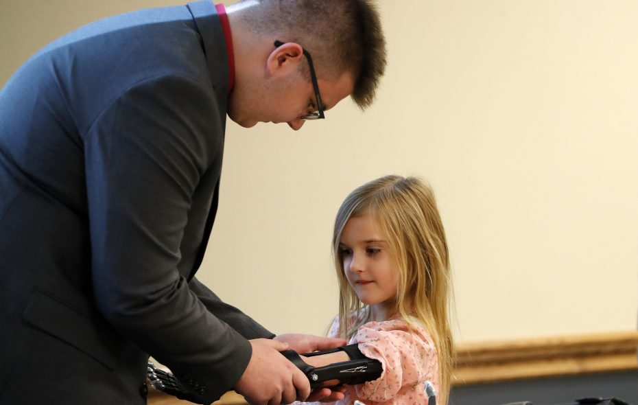 Briella Dennee, 7, receives her prosthetic hand from student Ian Hawkins during a ceremony at the Roswell Park Comprehensive Cancer Center in Buffalo on Saturday, Oct. 27, 2018. (Mark Mulville/Buffalo News)