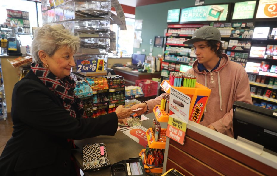Patricia Papafagos, of Williamsville, buys a ticket in the record-breaking $1.6 billion Mega Millions jackpot from Ryan Shanahan, a clerk at Sunoco Express Mart, on Maple Road in Amherst. (John Hickey/Buffalo News)