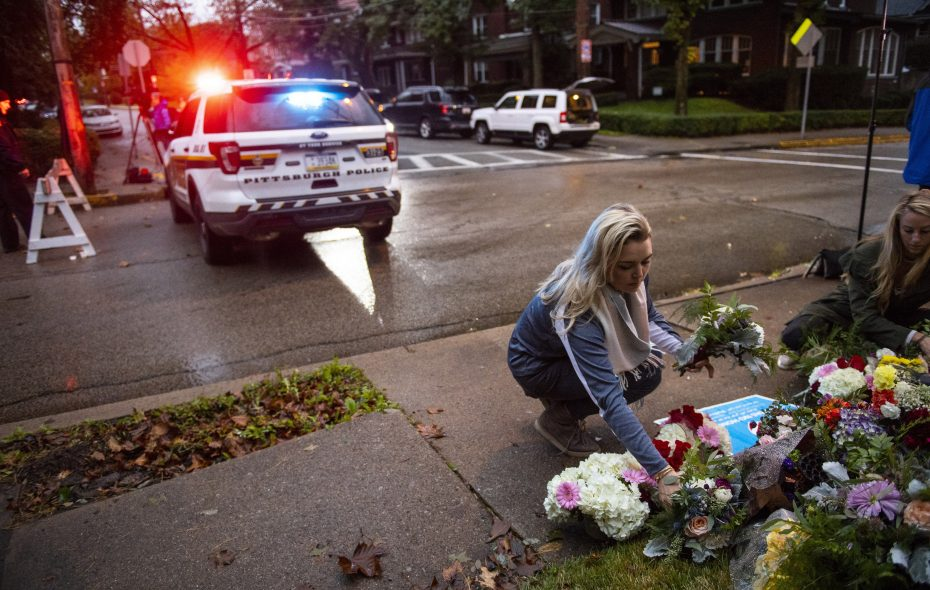 Adrienne Wager, left, and Shannon Haldeman place flowers near the Tree of Life Congregation, a day after 11 people died at the synagogue during a shooting rampage, in Pittsburgh, Oct. 28, 2018. Authorities on Sunday identified the 11 victims of the shooting in which a man armed with an AR-15-style assault rifle and three handguns shot into a morning worship service in the deadliest attack against the Jewish community in the United States in decades. (Michael Henninger/New York Times)