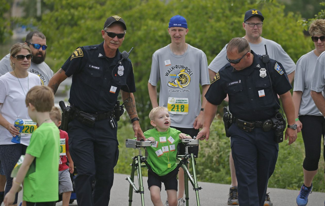 Two Buffalo Police officers, Tim Wagner, left, and Joe Donovan, right, with Easton Jordan, 6, walked Run/Walk/Roll in Lauren's Shoes with Easton until the end at Buffalo's Outer Harbor on Sunday, June 10, 2018. (Robert Kirkham/Buffalo News)
