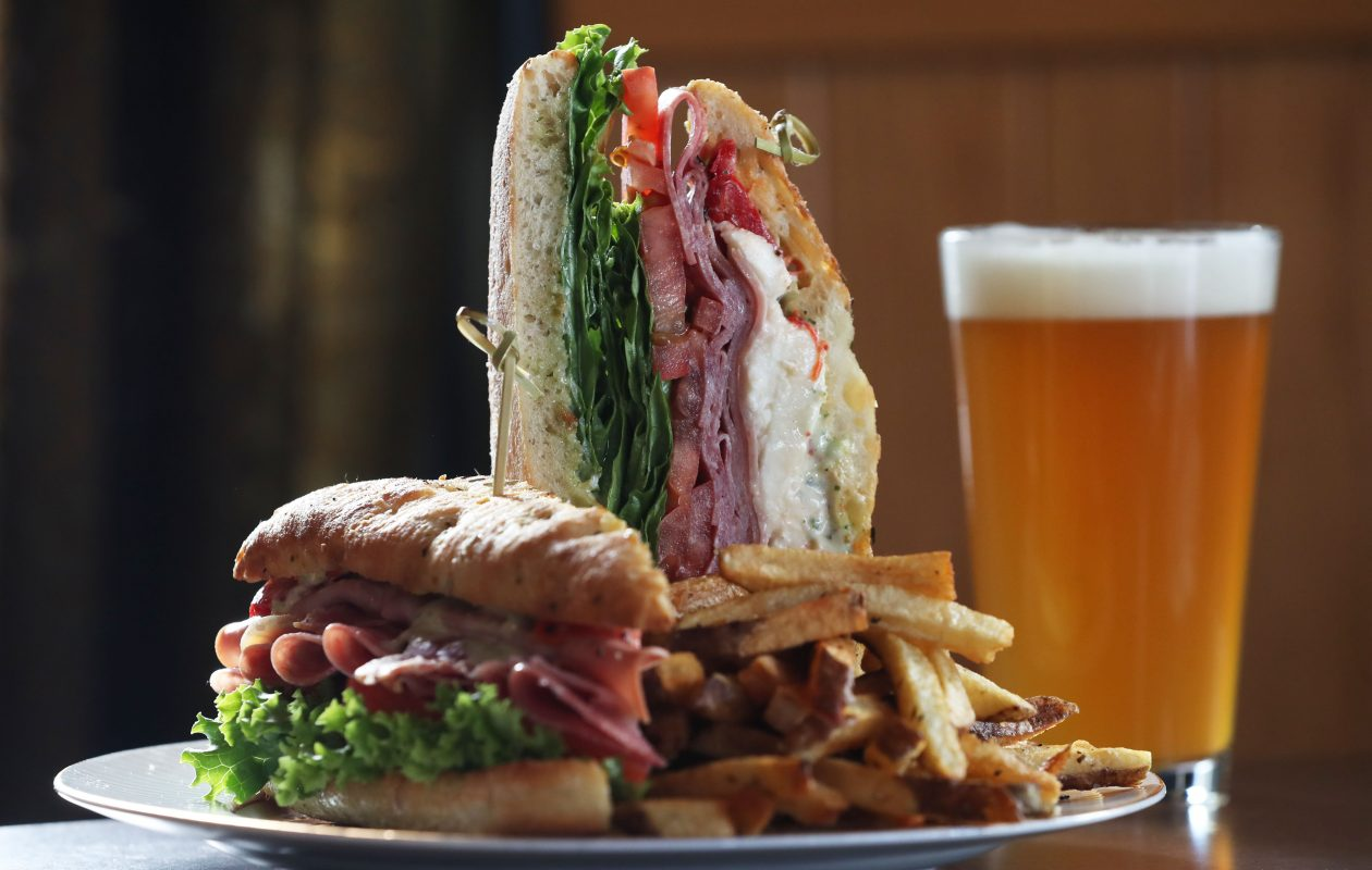 The legacy serves the Garlock's Deluxe Schiacciata, including sliced fresh mozzarella,  basil pesto mayonnaise, olive oil, lettuce, tomato, roasted red peppers, capicolla, mortadella and salami, on a toasted schiacciata roll. (Sharon Cantillon/Buffalo News)