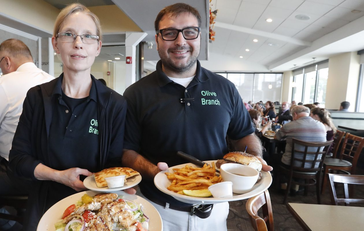 Owner Stavros Aronis holds a beef on weck and Floor Manager Debbie Zgoda has the chicken souvlaki served at the Olive Branch family restaurant. (Mark Mulville/Buffalo News)