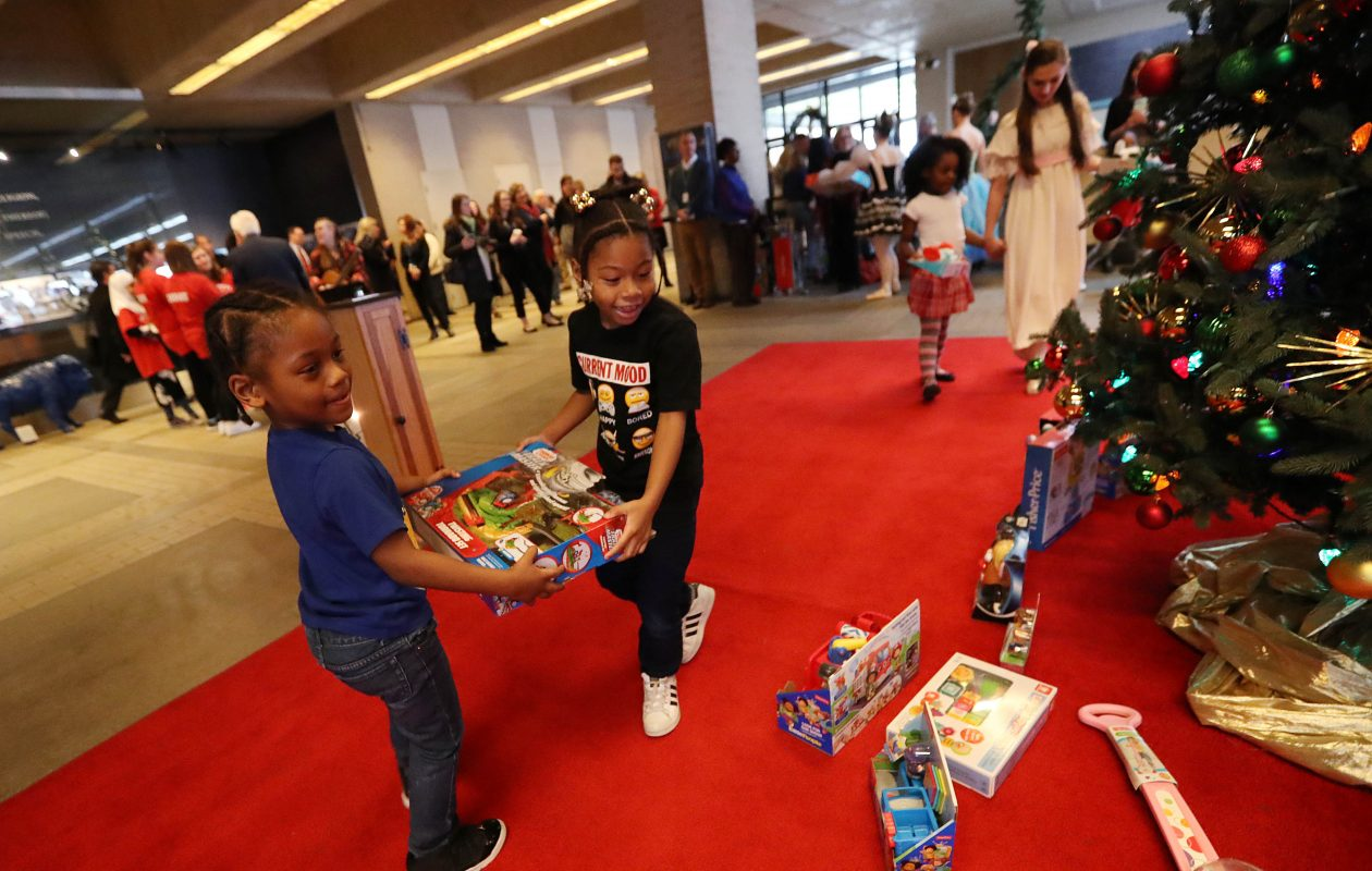 Ivan Parker Barnett, left, and Roziyah Williams of Houghton Academy put gifts under the Christmas tree as the 37th Annual News Neediest Fund kicked off this month in The Buffalo News lobby. (Sharon Cantillon/Buffalo News)