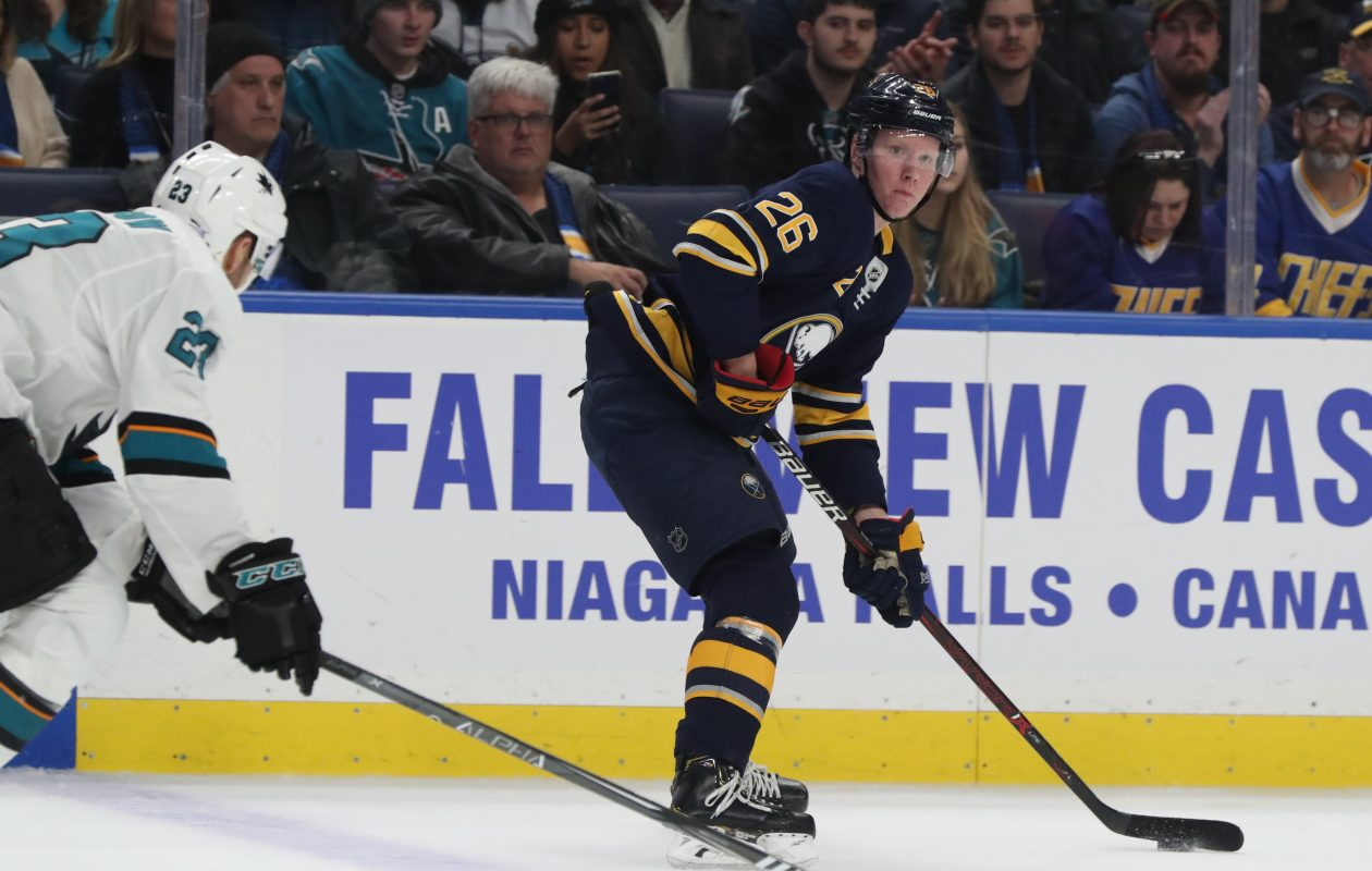 Sabres defenseman Rasmus Dahlin passes the puck past San Jose Sharks right wing Barclay Goodrow. (James P. McCoy/Buffalo News)
