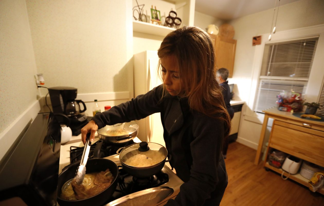 Angie Pena, left, and her sister Hilda Ramos make dinner at Ramos' Parkside home. (Mark Mulville/Buffalo News)