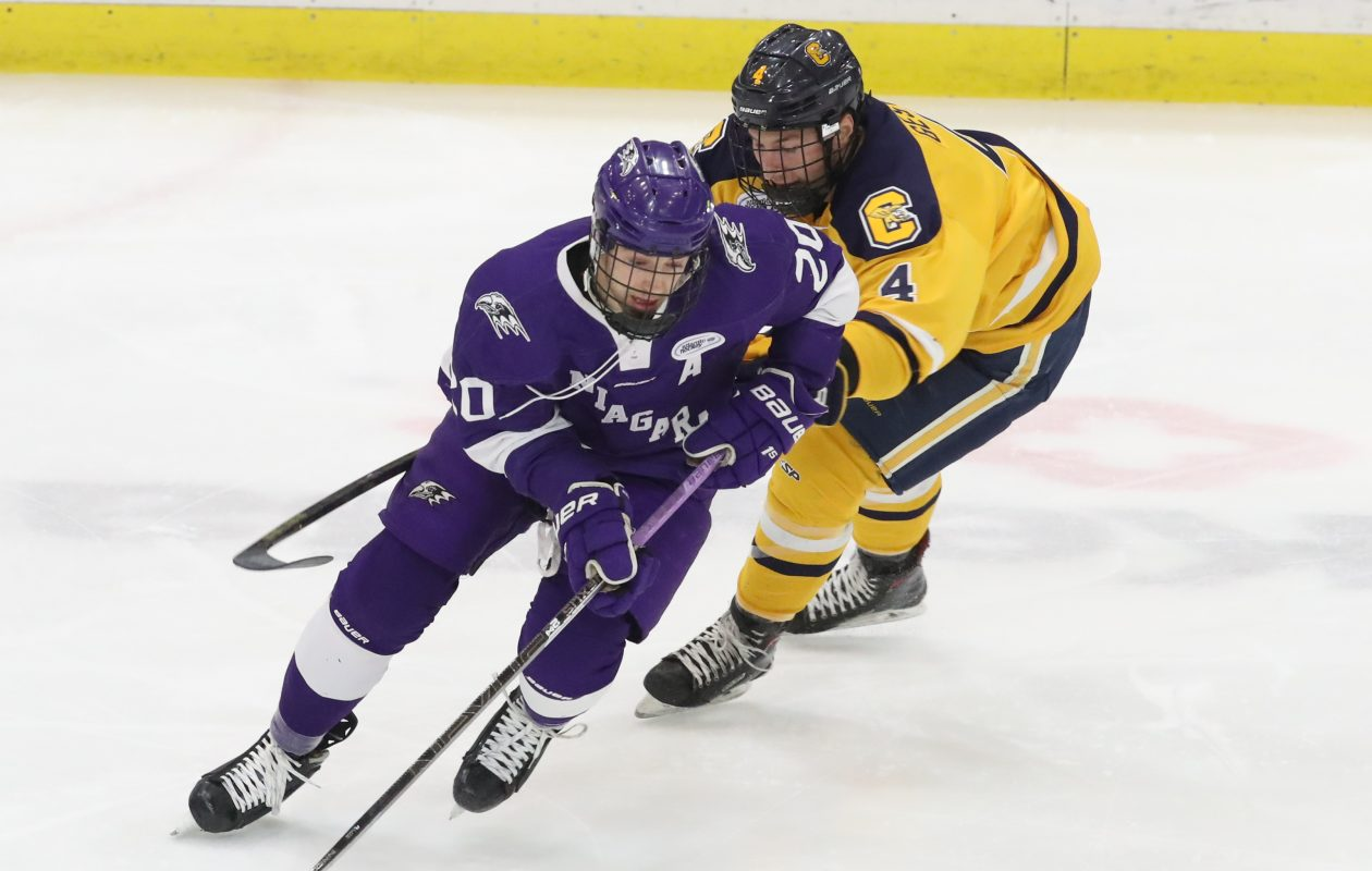 Niagara defenseman Noah Delmas, left, beats Canisius defenseman Logan Gestro to the puck (James P. McCoy/Buffalo News)