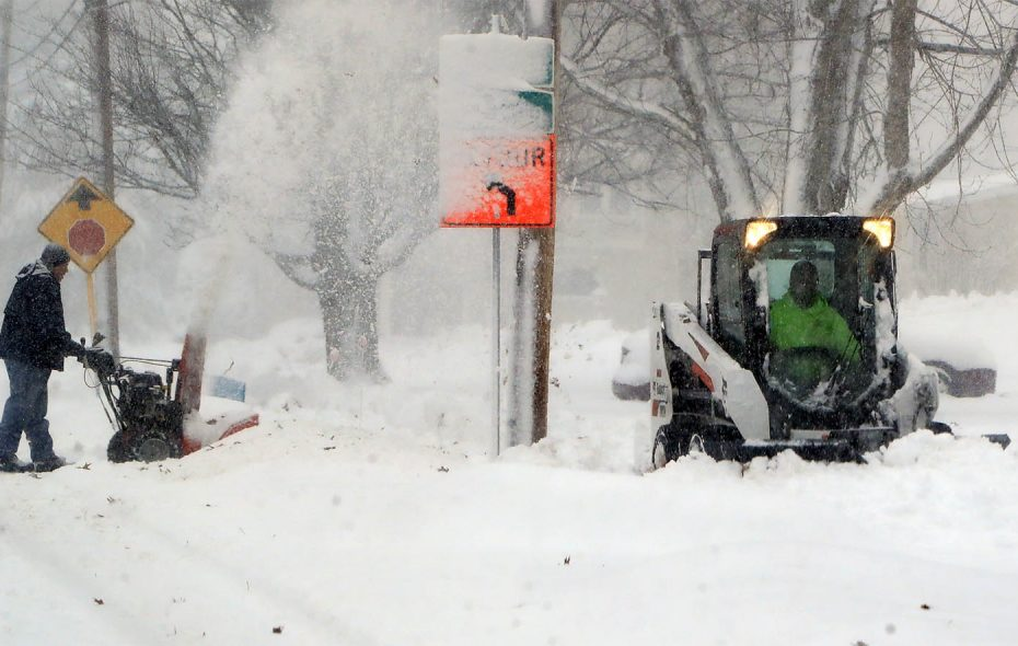 John Arbogast snowblows his driveway as a village plow clears the sidewalks along Mill Street in Springville, NY on Tuesday, Nov. 27, 2018. (Harry Scull Jr./Buffalo News)
