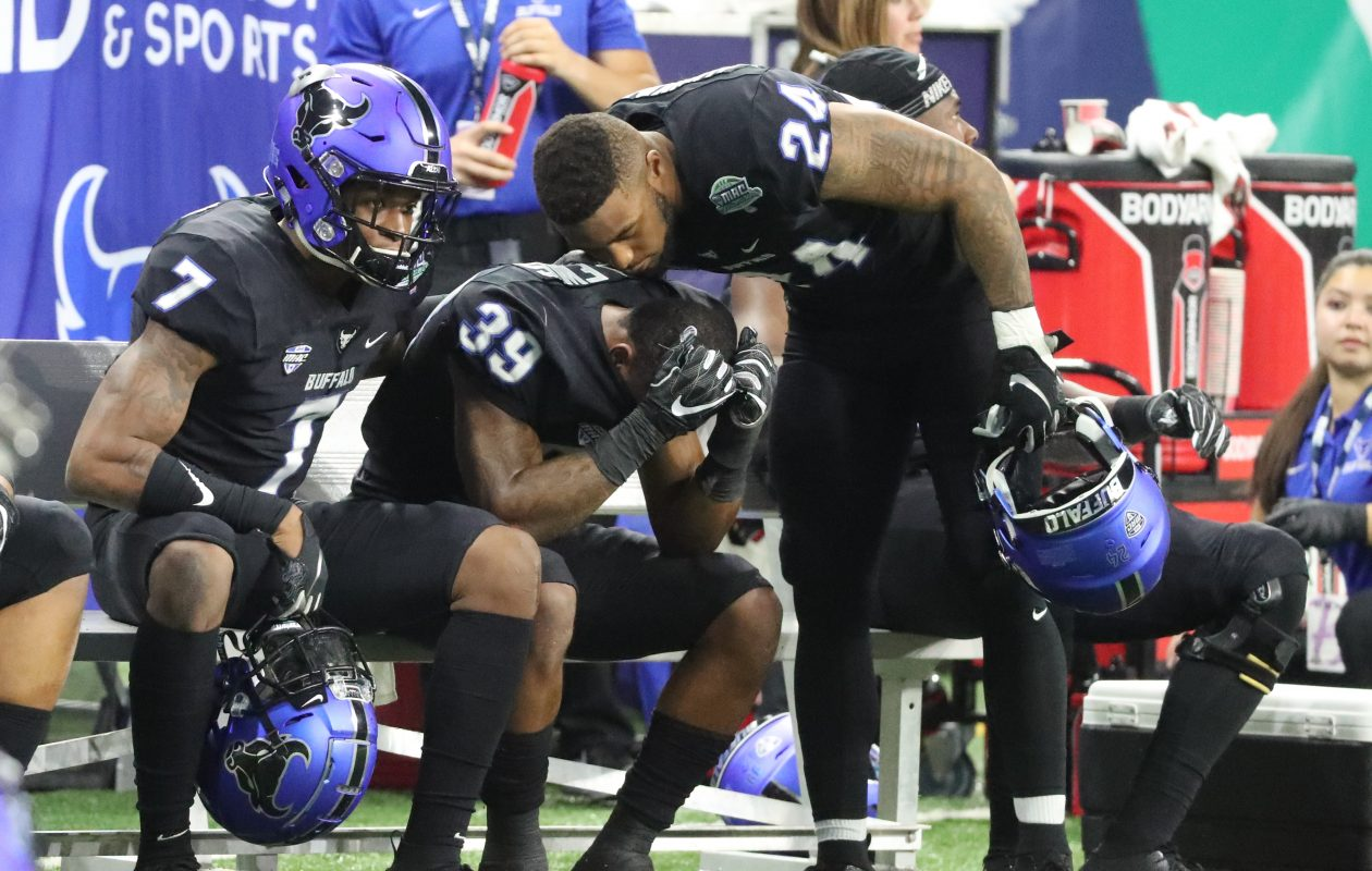 Bulls cornerback Cameron Lewis (39) is consoled on the bench after Northern Illinois Huskies beat the Buffalo Bulls 30-29 in the MAC Championship Game (James P. McCoy/Buffalo News)