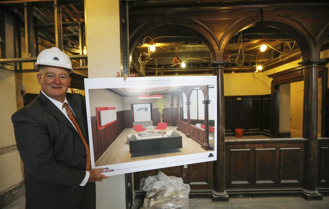 Martin Griffith, president of Bank on Buffalo, holds up a rendering of the lobby in the new Bank On Buffalo headquarters under construction on the seventh floor of the Electric Tower. (Derek Gee/Buffalo News)