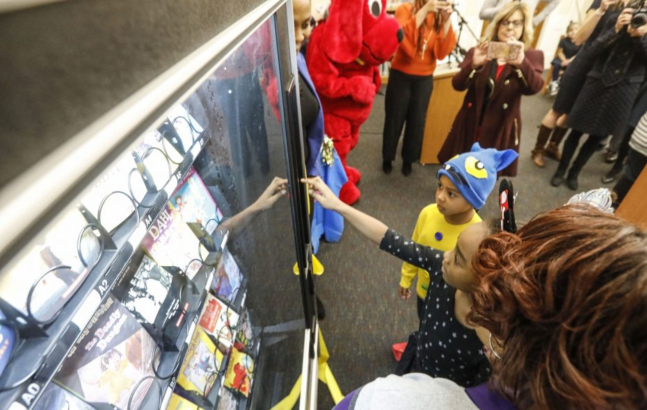 Third grade student Marshai Alston, 9, is the first to try out a new book vending machine in the library at the Arthur O. Eve School School of Distinction. (Derek Gee/Buffalo News)