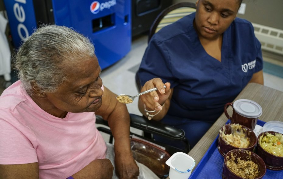 Aurea Fentress, left, a resident at Ellicott Center for Rehabilitation and Nursing in Buffalo, is fed her lunch by certified nursing aide Charnae Holmes on Aug. 1, 2018. (Derek Gee/Buffalo News)
