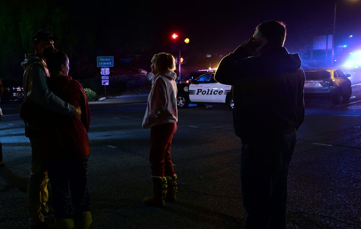 People stand and watch as the scene unfurls from the intersection of US 101 freeway and the Moorpark Rad exit as police vehicles close off the area outside a country music bar and dance hall in Thousand Oaks, west of Los Angeles, where a gunman opened fire late Nov. 7, 2018, killing at least 12 people, US police said. (Frderic J. Brown/AFP/Getty Images)