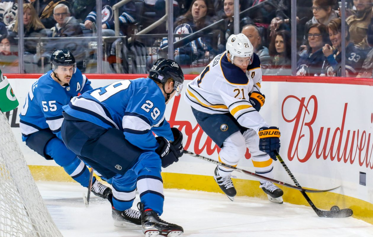 Kyle Okposo of the  Sabres plays the puck along the boards as Mark Scheifele (55) and Patrik Laine (29) of Winnipeg defend during first period action at the Bell MTS Place Friday.