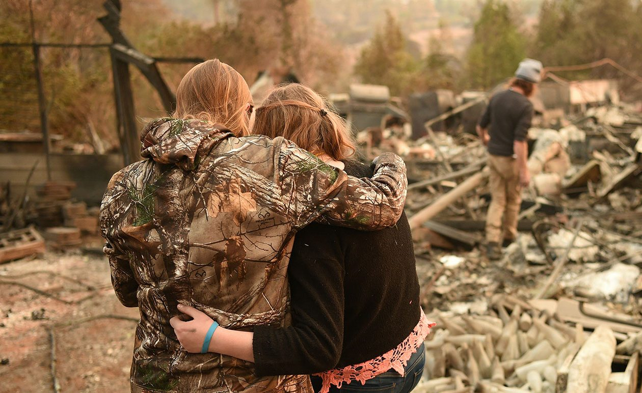 Kimberly Spainhower hugs her daughter Chloe, 13, while her husband Ryan Spainhower, background, searches through the ashes of their home in Paradise, Calif., on Nov. 18, 2018. (JOSH EDELSON/AFP/Getty Images file photo)