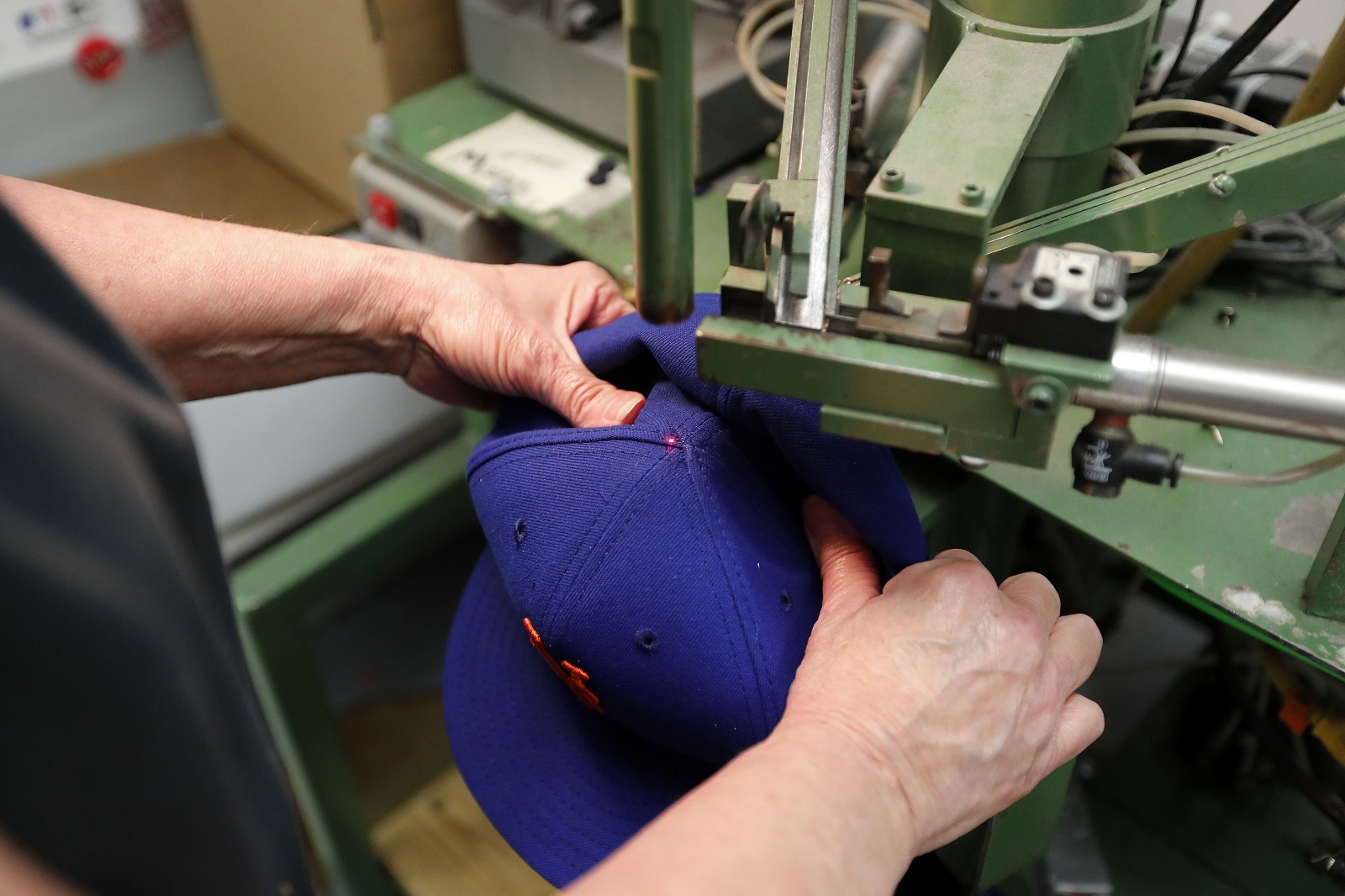 Flex team member Gayle Zabana attaches the button on the top of a cap at  the New Era factory in Derby in 2017. (Mark Mulville News file photo) f8f110f61e4a