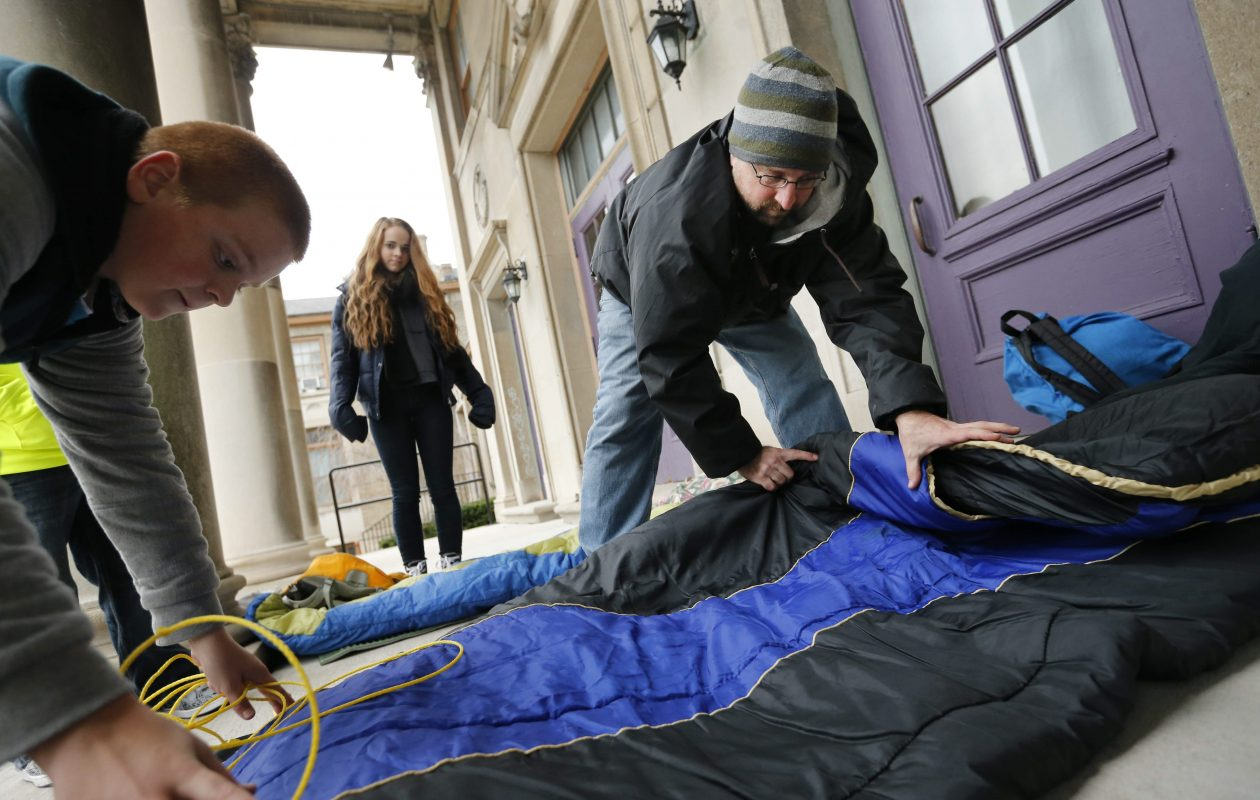 Pastor Eric Johns and his son, Alex, 12, left, set up sleeping gear on the porch in front of the Buffalo Dream Center on Lafayette Avenue as his daughter, Mikayla, 16, looks on, Friday, Nov. 27, 2015. (Derek Gee / Buffalo News file photo)