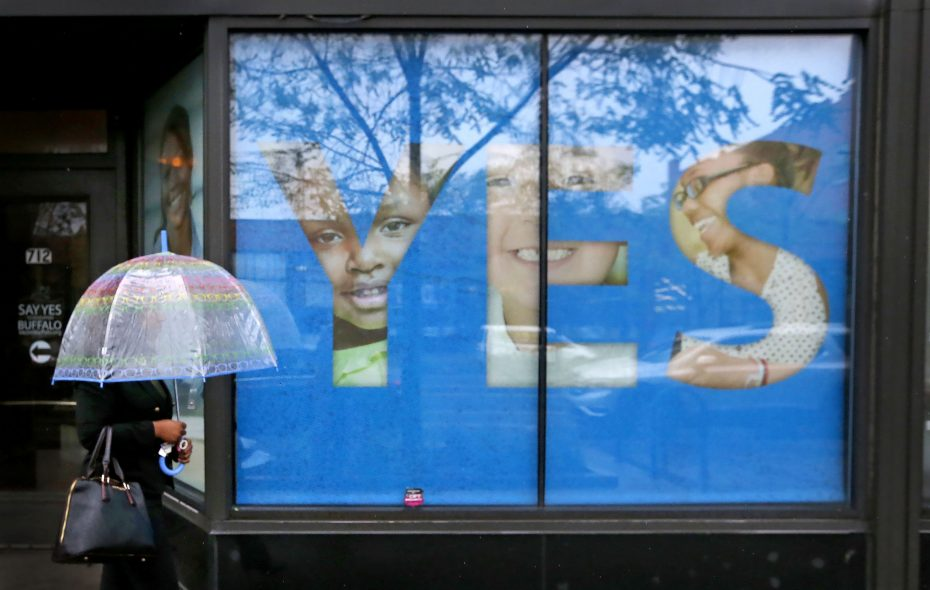 A pedestrian walks in front of the Say Yes to Education Buffalo office on Main Street. (Robert Kirkham/News file photo)