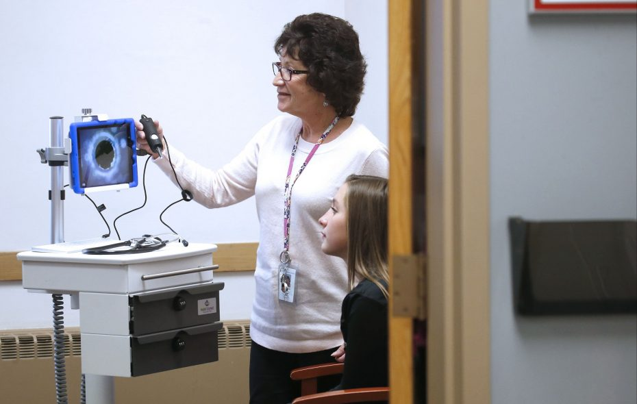 Frontier Middle School Registered Nurse Sue Andelora, uses the new Mobile Telemed machine with an otoscope attached to check for ear infections with student Kylie Sikorski, who volunteered to do a test examination. The school will soon employ this apparatus to send real time video and vitals evaluations to medical professionals on the other end.  (Robert Kirkham/Buffalo News)