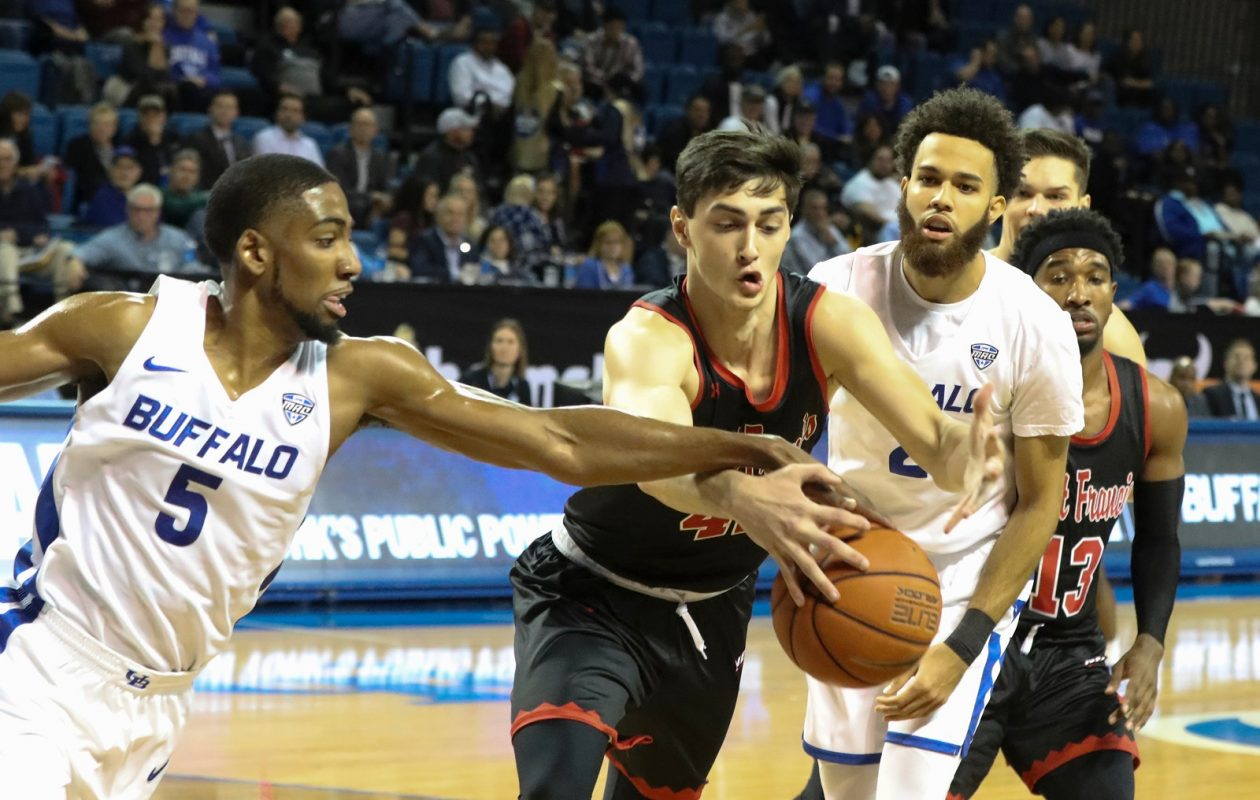 Buffalo Bulls guard CJ Massinburg (5) battles St. Francis (Pa.) Red Flash forward Mark Flagg (42) for the ball at during action at Alumni Arena. (James P. McCoy/News file photo)