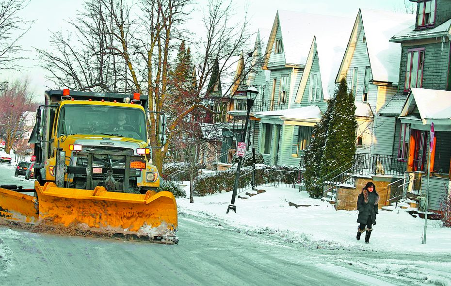 A city plow clears light snow on Heath Street in the University District. (John Hickey/News file photo)
